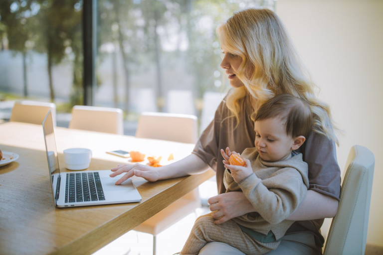 women holding child on lap whilst working